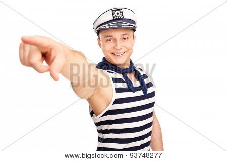 Young cheerful sailor pointing forward with his finger and looking at the camera isolated on white background