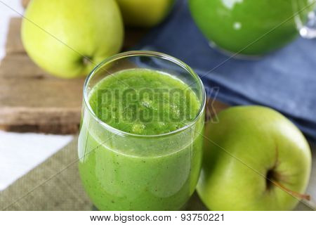 Healthy green smoothie with green apples on sackcloth, closeup