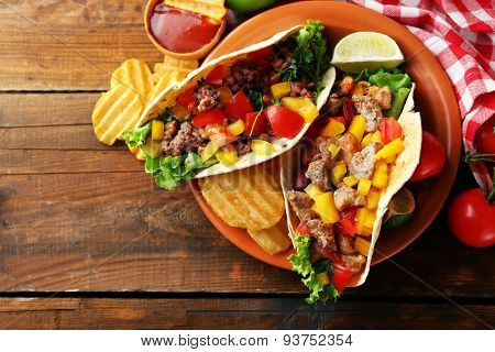 Homemade beef burritos with vegetables, potato chips on plate, on wooden background