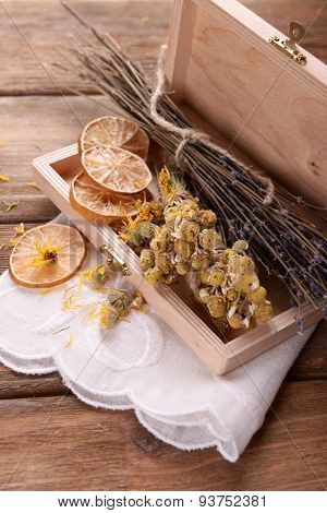 Different dried herbs and lemon on table close up