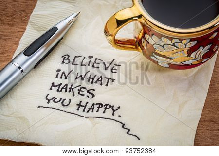 Believe in what makes you happy - handwriting on a napkin with cup of coffee