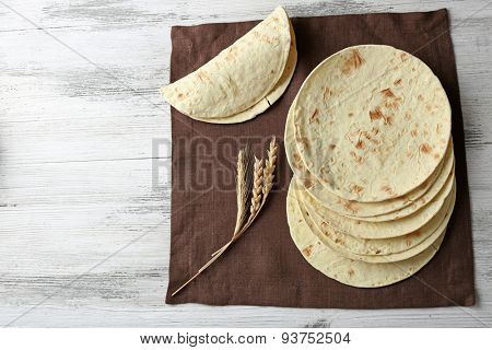 Stack of homemade whole wheat flour tortilla on napkin, on wooden table background