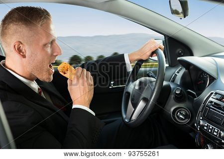 Businessman Eating Snack While Driving