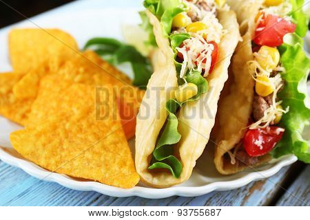 Tasty taco with nachos chips  and vegetables on plate close up