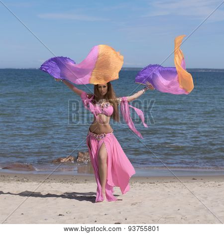 Belly Dancer In Colorful Costume On The Beach With Fans