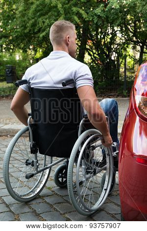 Man In Wheelchair Next To His Car