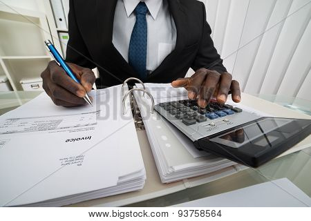 Businessman Calculating Invoices