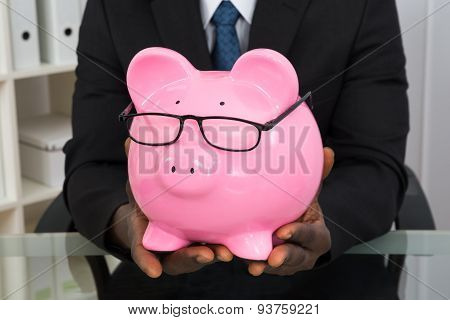 Businessman Holding Piggybank With Eyeglasses