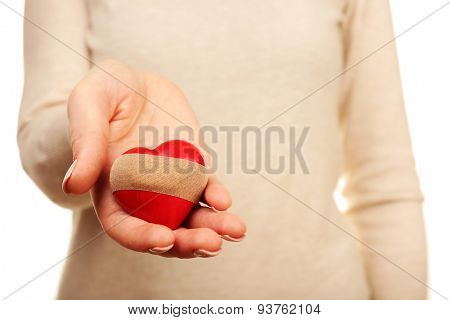 Woman holding heart with plaster close up