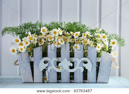 Beautiful bouquet of daisies in ornamental flowerpot on wooden background