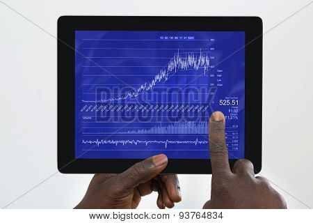 Person Analyzing Graph On Digital Tablet