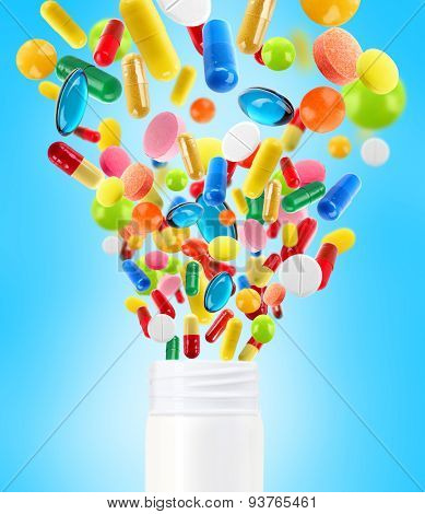 Different pills flying away from open plastic bottle on bright blue background