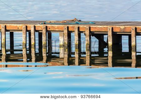 Wooden Pier With Chords and water reflections