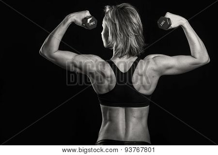 Strong, sexy girl posing on black