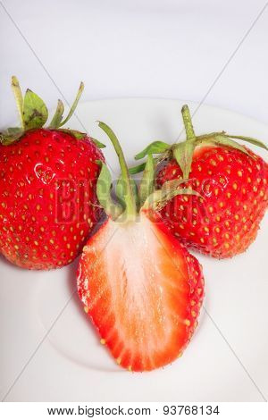 Half of ripe and juicy strawberries on a plate with two whole berries. close-up.