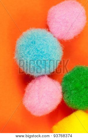Arrangement of vivid colorful fluffy fuzzy textile soft balls on vibrant orange paper background