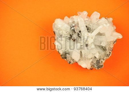 White quartz crystal block on vivid orange paper background with soft shadows