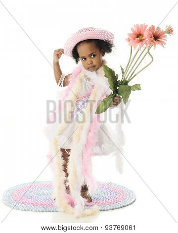 An adorable barefoot two year old standing in pearls and boas.  She carries a small bouquet of tall pink flowers.  On a white background.