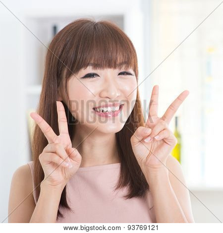 Portrait of attractive Asian girl showing peace or v hand sign. Young woman indoors living lifestyle at home.
