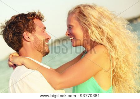 Romantic couple in love kissing happy at beach sunset. Young happy man and woman on in romance on summer beach during honeymoon vacation holidays travel.