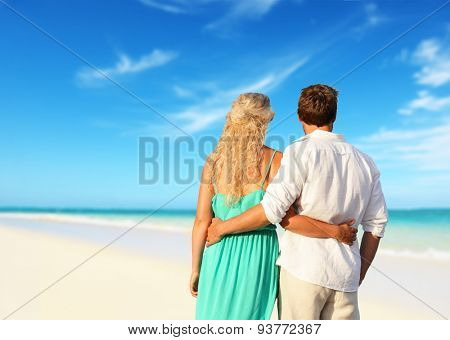 Romantic couple in love enjoying summer at beach. Young happy woman and man lovers embracing and hugging in romance on summer beach during honeymoon vacation holidays travel.