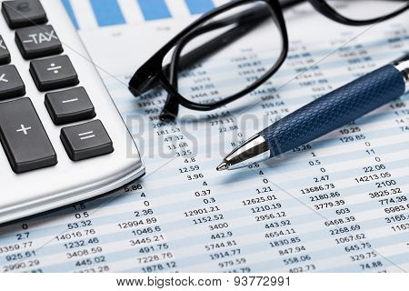 Calculator With Pen And Eyeglasses On Data Sheet