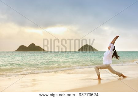 Yoga woman meditating in warrior pose relaxing outside on beach at sunrise. Female yoga girl working out training in serene ocean landscape. Lanikai beach, Oahu, Hawaii, USA.