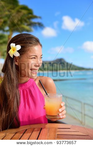 Cocktail woman drinking alcohol drinks at beach bar resort in Waikiki, Honolulu city, Oahu, Hawaii, USA. Asian girl tourist looking at camera toasting a glass of strawberry Hawaiian drink at sunset.