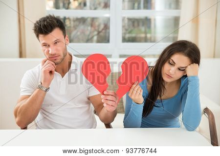 Sad Couple Holding Broken Heart