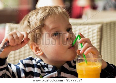 The boy has breakfast. Kid drinking orange juice
