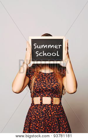 University College Student Holding A Chalkboard Saying Summer School