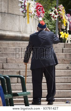 NEW YORK - MAY 25 2015: A US veteran salutes after laying a wreath of flowers at the Memorial Day Observance service held at the Soldiers and Sailors Monument in Manhattan during Fleet Week NY 2015.