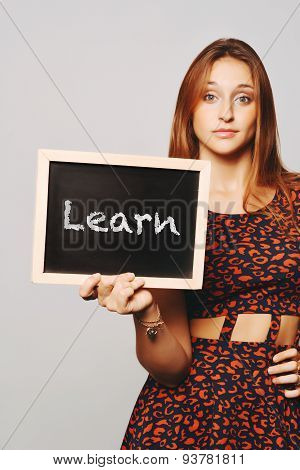 University College Student Holding A Chalkboard Saying Learn