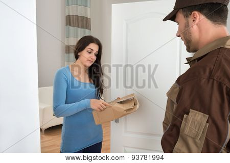 Woman Holding Damaged Package From Delivery Man