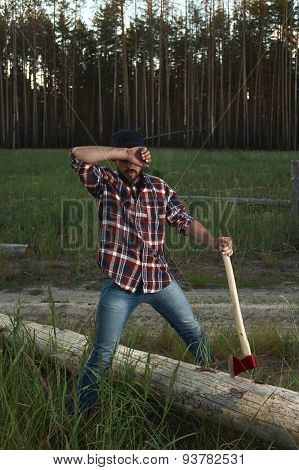 Bearded Lumberjack Holding A Big Ax In Hand And Wipes The Sweat