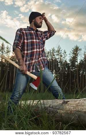 Bearded Lumberjack Holding A Big Ax In One Hand And Wipes The Sweat Anothet Hand