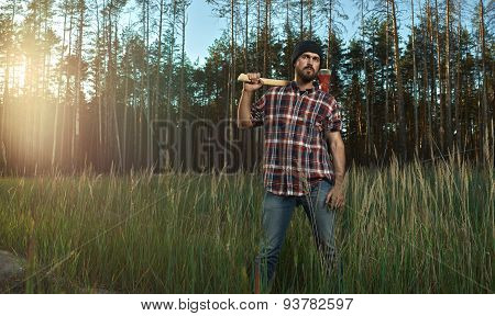Bearded Lumberjack In Hat Holding A Big Axe On Shoulder In Forest
