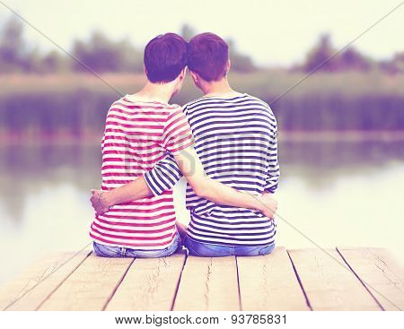 Male Couple In Love, Sitting On Wooden Pier At Riverbank