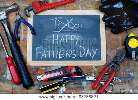 A blackboard used for dad's to do list has been crossed out and a Happy Fathers Day message has been written. Yellow, red and orange tools are scattered in front of the board.