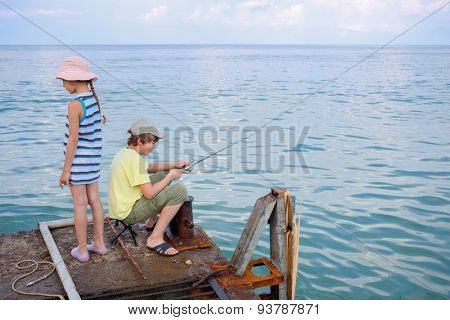 brother and sister go fishing on the docks