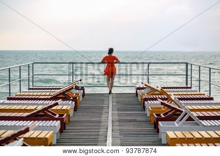 woman among the deck chairs on the pier in the sea