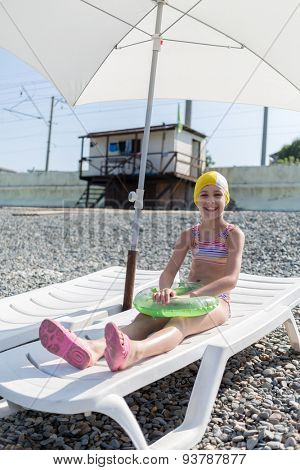 girl in a bathing cap on a lounger on the beach