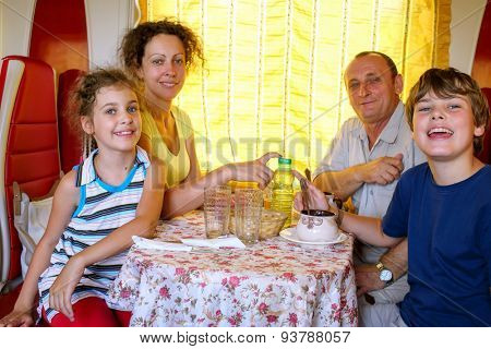 family of four posing at a table in the dining car of the train