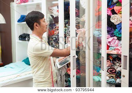 Asian man tailor choose fabric fashion clothes wardrobe dress designer