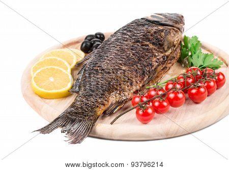 Fried carp on wooden platter.
