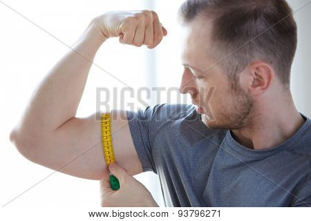 sport, fitness, lifestyle, bodybuilding and people concept - close up of male hands with tape measuring bicep