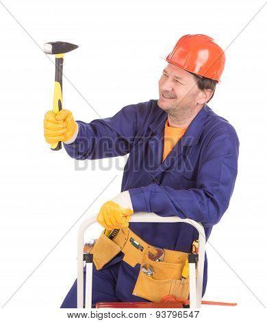 Worker in hard hat holding hammer.
