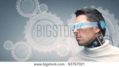 people, technology, future and progress - man with futuristic glasses and microchip implant or sensors over gray background with cogwheel mechanism projection