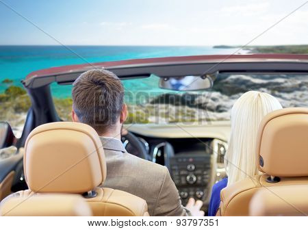 drive, auto trip, travel, tourism and people concept - close up of couple driving in cabriolet car from back over sea shore background