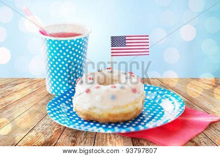american independence day, celebration, patriotism and holidays concept - close up of glazed donut decorated with flag and juice in disposable tableware on wooden table over blue lights background